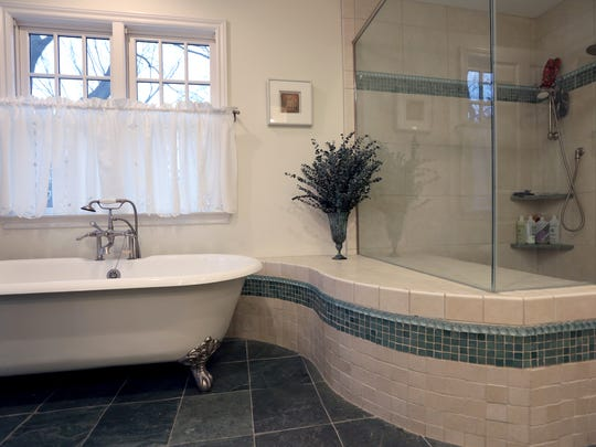 Master bathroom with walk-in shower and claw foot tub.