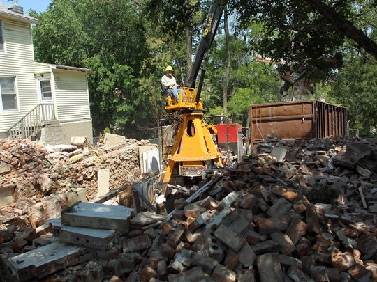 Crews tear down the former Book Shop at 608 S. Dubuque St. on May 27. The building was the last of the Civil War-era cottages to be torn down, after the former Suzie's Antiques was torn down earlier in the day and the former Moy Yat Ving Tsun Kung Fu Studio was demolished on Dec. 26.