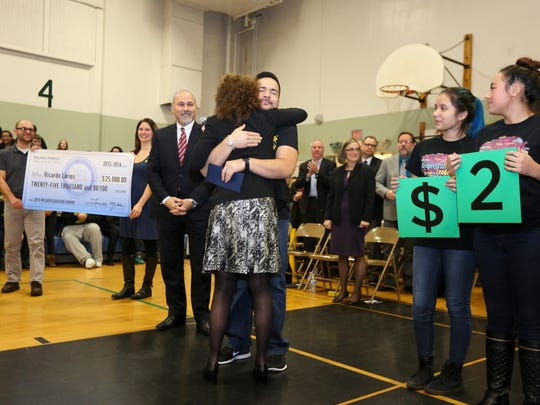 Waldo Middle School teacher Ricardo Larios embraces Dr. Jane Foley of the Milken Education Foundation as he is awarded the prestigious Milken Educator Award on Wednesday, Jan. 6, 2016, in Salem.