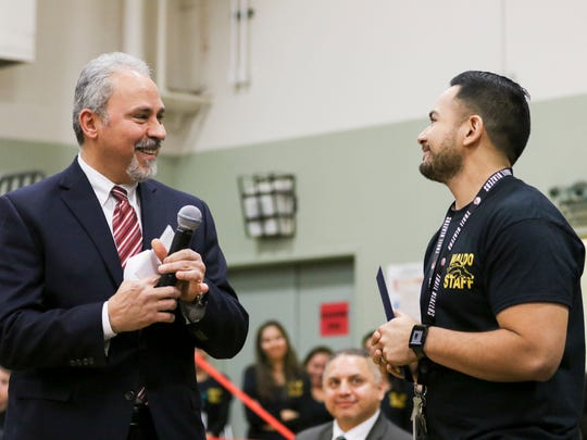 Deputy Superintendent Salaam Noor (left) congratulates Waldo Middle School teacher Ricardo Larios (right) on receiving the prestigious Milken Educator Award on Wednesday, Jan. 6, 2016, in Salem. The award is given to teachers committed to excellence in education and it comes with a $25,000 unrestricted financial prize.