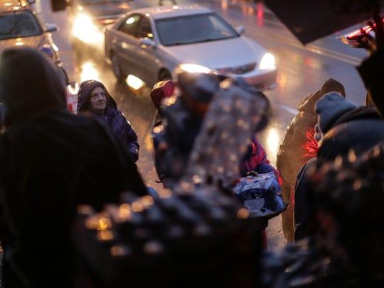Flint community members wait as members of We the People