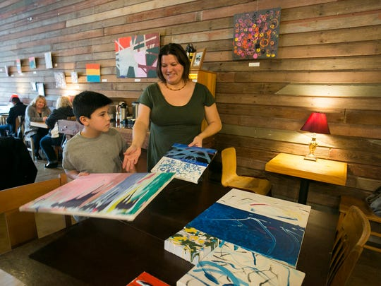 Solen Lewis, 9, and his mom Jeanette figure out which of his paintings to hang on the wall of West Salem's Urban Grange Coffee, as they replace some of Lewis' artwork that has already sold. The young painter is donating 100 percent of his proceeds to Salem Dream Center, and he has already raised $525 for the local non-profit.