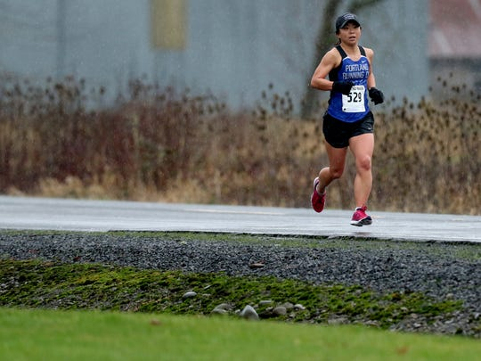 A racer runs in the rain during the 17th annual Cascade Half Marathon, 10K and 2-mile at Cascade Junior High School in Turner, Ore., on Sunday, Jan. 17, 2016.