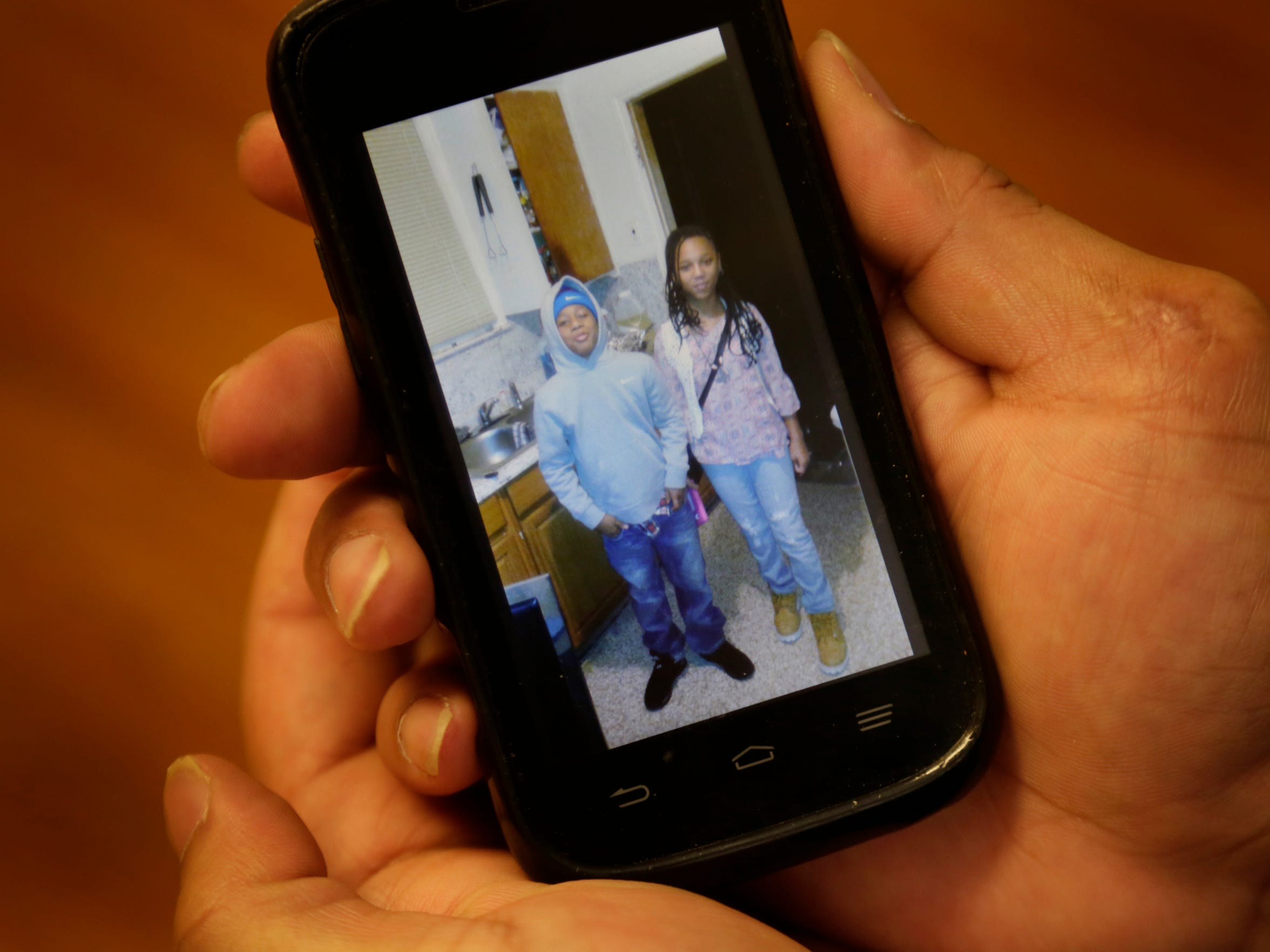 Lamar McGaughy, 38, of Detroit, shows a photo of his two children during a meeting at the Detroit Center for Family Advocacy in Detroit.