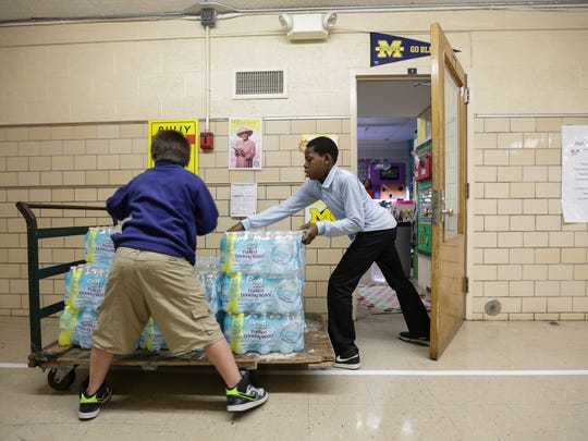 Freeman Elementary School 6th-graders Kashif Nance, right, and John Orr deliver cases of bottled water donated to their school to classes in October. Freeman had a water sample tested at 101 parts per billion  for lead exceeding, the EPA's action level of 15 parts per billion.