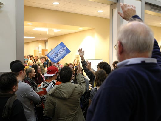 Democratic caucusgoers raise their hands as votes are counted at the Iowa City Public Library on Monday, Feb. 1, 2016.