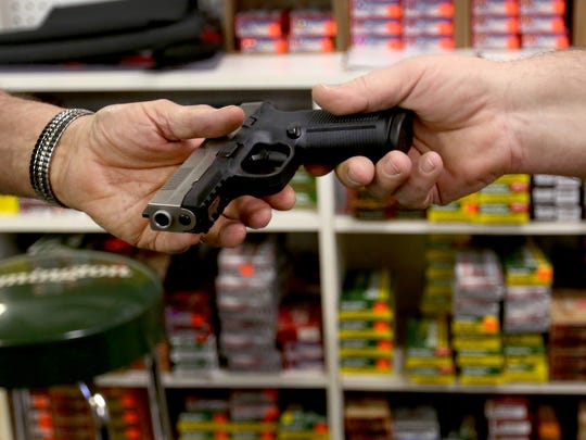 Co-owners Ron Redding and Doug Raaf look at a gun at Gun Crafters, Firearms and More in Salem on Tuesday, Feb. 2, 2016.