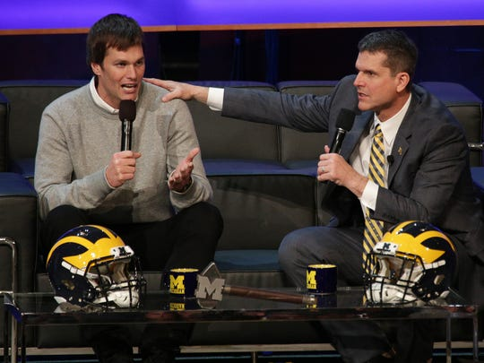 """U-M football coach Jim Harbaugh, right, talks with New England Patriots quarterback Tom Brady during the """"Signing of the Stars"""" event in Ann Arbor."""