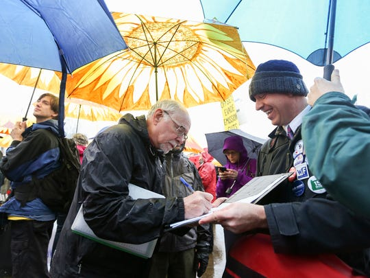 Rob Fullmer holds a sign up sheet for initiative petition 28 as Eugene resident Mike Brinkley signs his name at a rally for a Healthy Climate and Clean Energy Jobs on the steps of the Capitol on Wednesday, Feb. 3, 2016. The petition is gathering signatures to place a corporate income tax measure on the November 2016 ballot.