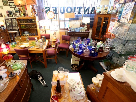 Nicky, the Boston terrier of Timeless Antiques owner Barbara Johnson, sits in the shop in Aurora.