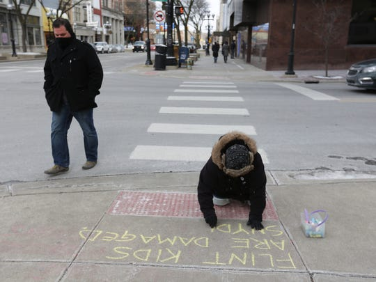 "Susan Fecteau, 58, of Ann Arbor, writes a message in chalk on Thursday, February 11, 2016, on a downtown Ann Arbor sidewalk.expressing her anger to Gov. Rick Snyder over his handling of the Flint water crisis. Snyder and his wife live in a two-story loft above a storefront in downtown Ann Arbor.  ""I was so outraged, The chalk gave me a voice,"" says Fecteau, 58."