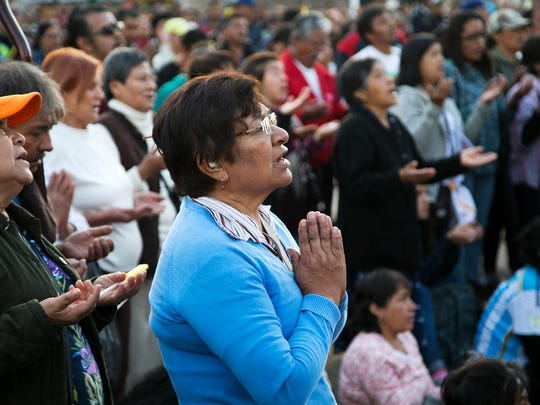 Maria Teresa of Mexico City, Mexico, prays with others as they watch Pope Francis celebrate Mass on a jumbo screen about a half mile away from the Basilica of Guadalupe where Pope Francis was celebrating the Mass in Mexico City, Mexico, on Saturday, Feb. 13, 2016.