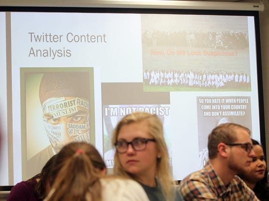 Images are projected during a class discussion in Lisa Covington's Introduction to Sociology course at Van Allen Hall on Thursday, Dec. 10, 2015.
