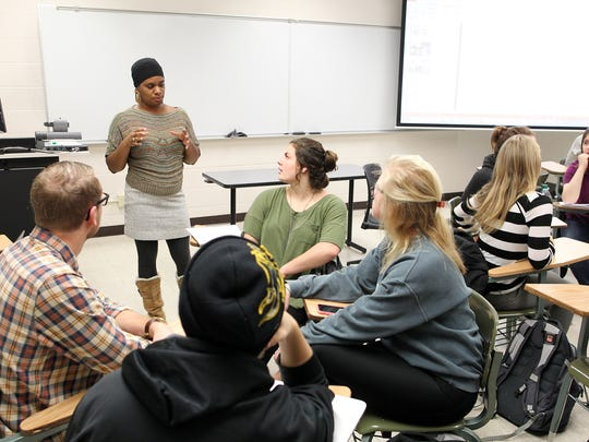 Lisa Covington works with students in her Introduction to Sociology course at Van Allen Hall on Thursday, Dec. 10, 2015.