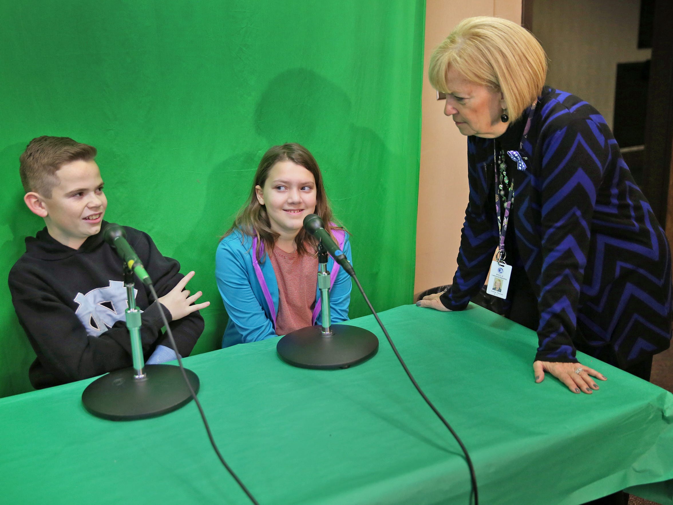 Connie Thomas visited with students Charlie (left) and Ella preparing to read the morning news at Amy Beverland Elementary on Tuesday, Feb. 16, 2016.
