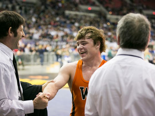 Willamina's Austin Howard celebrates with his coaches after defeating Vale's Garrett DeVos at the OSAA state wrestling tournament on Saturday, Feb. 27, 2016, at Memorial Coliseum in Portland, Ore.