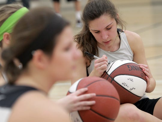 Mid-Prairie's Alex Rath signs a teammate's state tournament basketball after practice on Friday, Feb. 26, 2016.