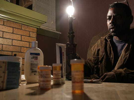 Darryl Wilson sits behind multiple creams and medications for rashes that cover his body on Friday February 5, 2016 that he has to apply twice a day due to using the Flint water before moving into his current home where he doesn't have running water. 'Only way I don't be scratching is when I'm up doing something and don't think about it. I don't think about it when I'm laying around but it's just a natural reaction now. I scratch till I get a scab on it. Once it dries and get hard now I got to pick it.'