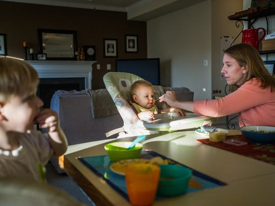Katie Markey McLaughlin feeds Lily, 9 months, as her son, Luke, also eats dinner with her husband Dave at their home in Springfield Township. Markey McLaughlin said high childcare costs were a factor in her decision to leave a full-time job, choosing instead to work several part-time jobs while raising a family.