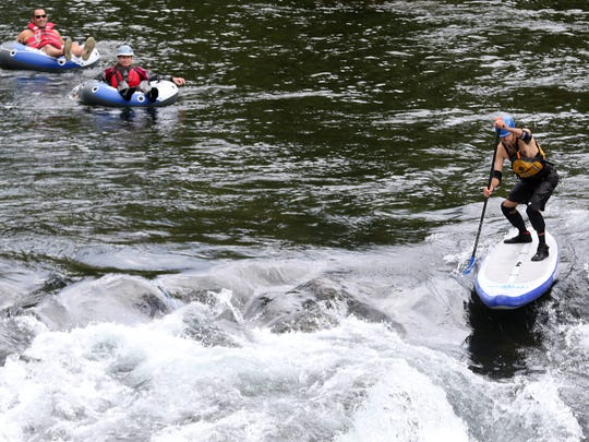 A paddle boarder and rafters prepare to go over the Mill City Falls during the Ruckus on the River Santiam Whitewater Festival in Mill City in 2015.