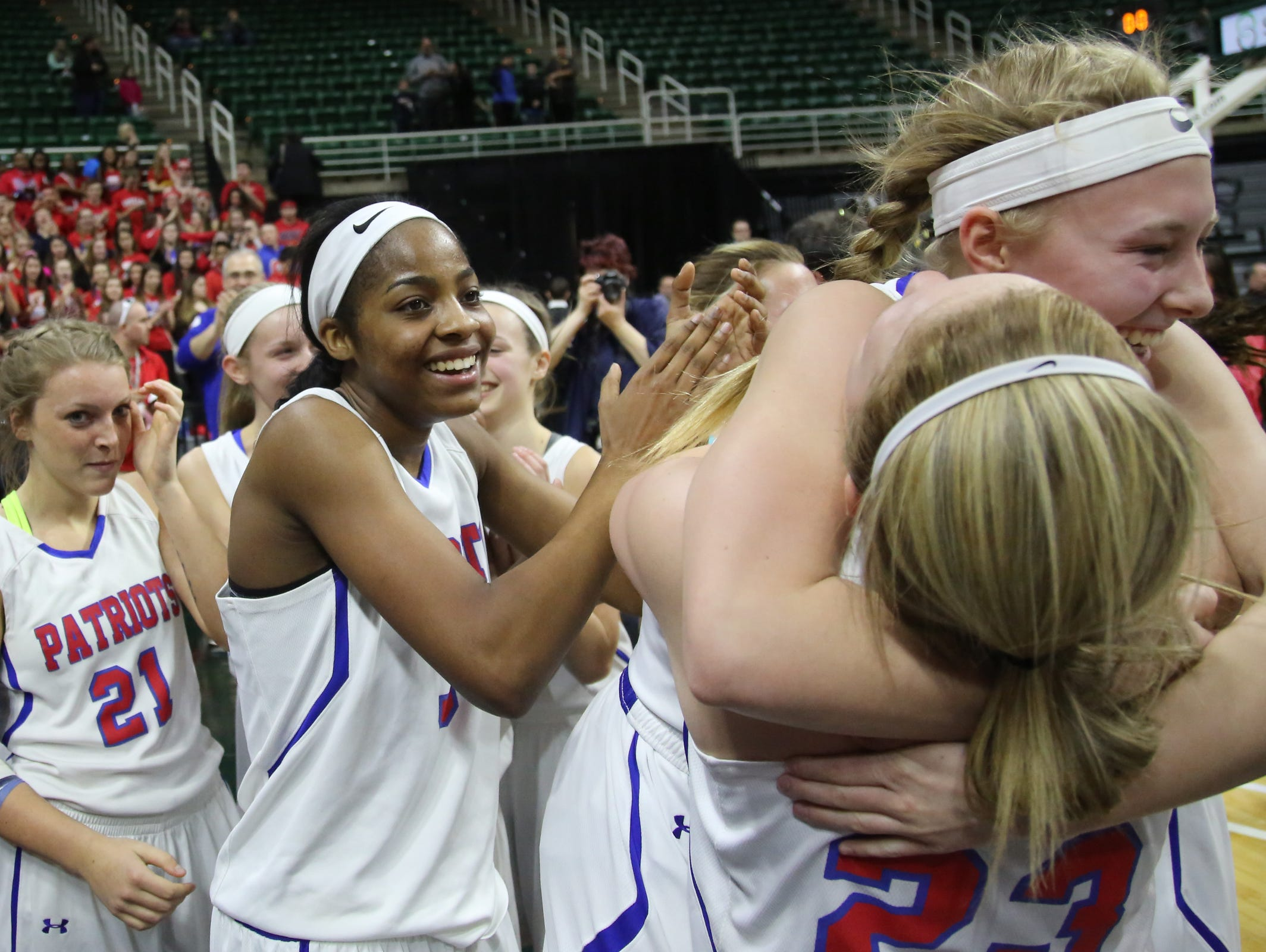 Warren Cousino's Aubrey Holman, Kierra Fletcher, and teammates celebrate defeating Hudsonville 60-45, during the MHSAA girls basketball Class A game 2 semifinals at the Breslin Center in East Lansing, Mich. on Friday, March 18, 2016.