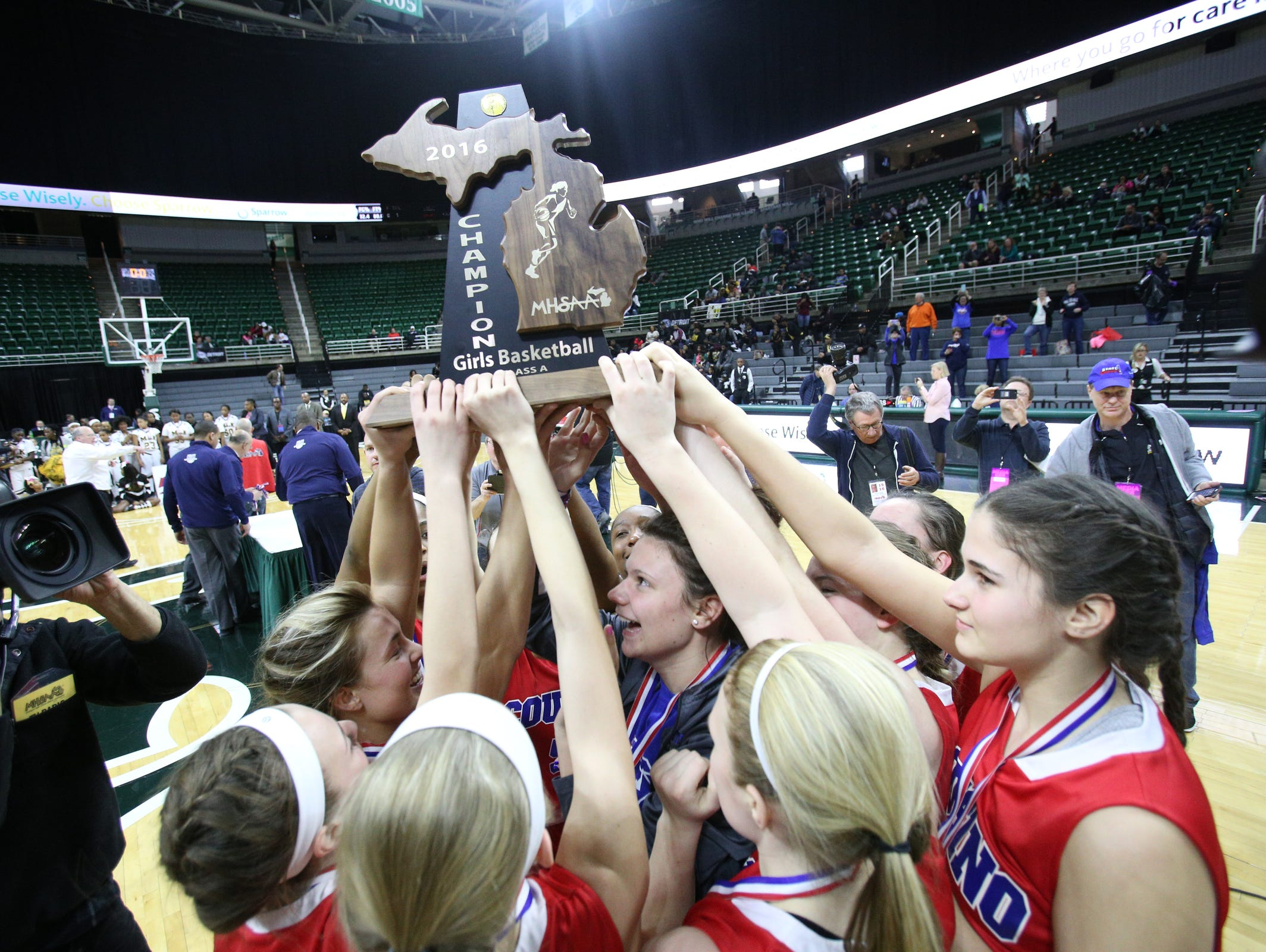 Warren Cousino holds up the trophy after defeating Detroit Martin Luther King 67-65, during the MHSAA girls basketball Class A finals at the Breslin Center in East Lansing on Saturday, March 19, 2016.
