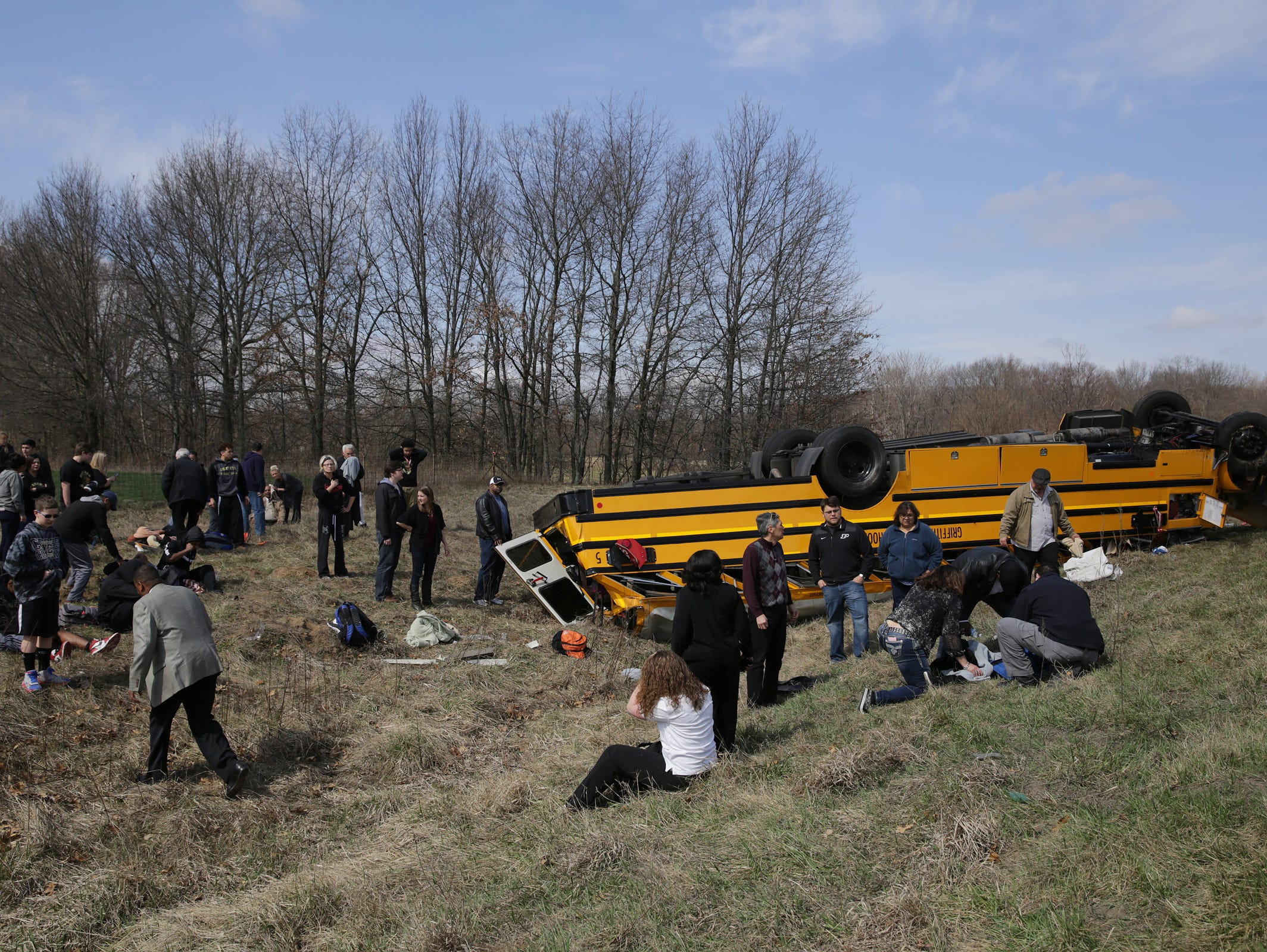 People on the scene of a school bus accident attend to the injured. The bus carrying the Griffith boys basketball team overturned Saturday along Interstate 65 on the way to a semifinal game against Marion at Lafayette Jefferson.