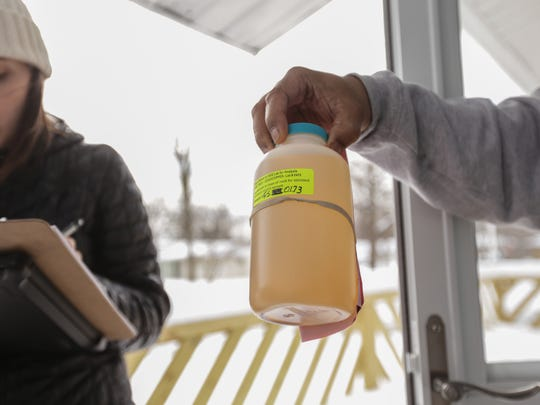 Flint resident Michael Anderson, 51 hands a discolored water sample to DEQ environment quality analyst Anne Tavalire on Wednesday March 2, 2016 as Tavalire and Flint ambassadors go collecting water samples from Flint residents in the sentinel site program by the Department of Environmental Quality. The program launched by the DEQ and EPA was created to test Flint drinking water supply at roughly 400 representative sites around the city in an effort to see whether the city's switch back to a Detroit water supply has reduced lead levels.