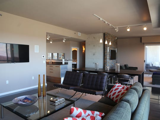 The condo has wood and tile flooring and exposed concrete