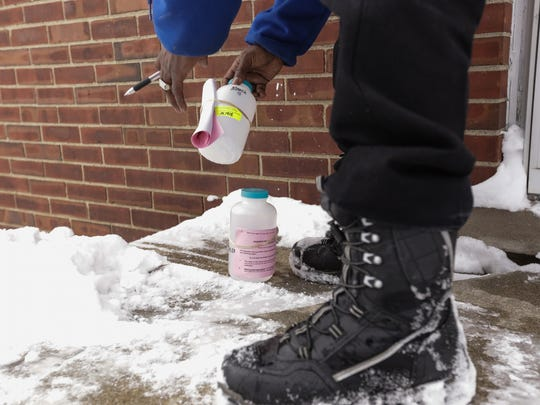 Flint resident Ronnie Russell puts down a new sample bottle at a Flint resident's home for the next sampling while collecting water samples on Wednesday March 2, 2016 that are included in the sentinel site program by the Department of Environmental Quality. The program launched by the DEQ and EPA was created to test Flint drinking water supply at roughly 400 representative sites around the city in an effort to see whether the city's switch back to a Detroit water supply has reduced lead levels.