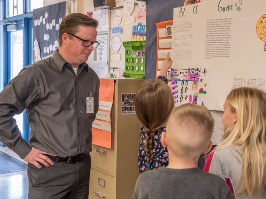 Downtown Development Director John Hart reviews some North Pennfield Elementary second-grade students'  ideas for new businesses in the Battle Creek area in March.