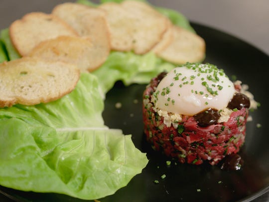 Beef tartare with poached egg, black garlic and parmesan, served with a side of crostini and butter lettuce. From Standby, a cocktail lounge and restaurant in the Belt Alley in downtown Detroit.