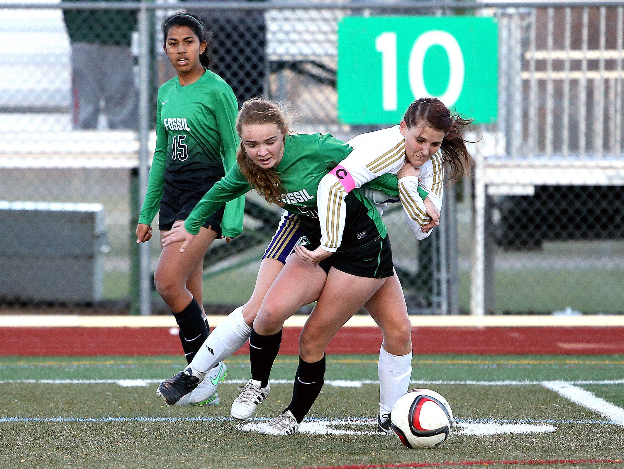 Fossil Ridge's Remi Clarke and Fort Collins' Nicole Dietrich fight for a loose ball during the Lambkins' 2-0 win over the SaberCats at Rocky Mountain High School on Tuesday, April 5, 2016.