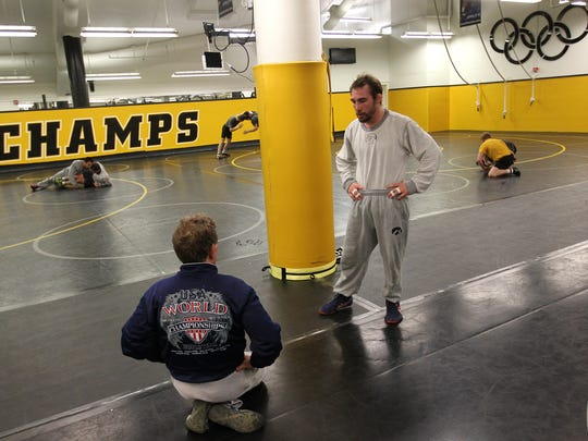 Former Hawkeye Daniel Dennis talks with coach Mike Duroe during practice at Carver-Hawkeye Arena on Thursday, March 31, 2016. Dennis heads into the U.S. Olympic Wrestling Team Trials ranked third in freestyle at 125.5 pounds (57 kilos).