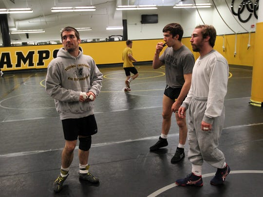 Former Hawkeyes Brent Metcalf, left, and Daniel Dennis, right, chat before practice at Carver-Hawkeye Arena on Thursday, March 31, 2016.