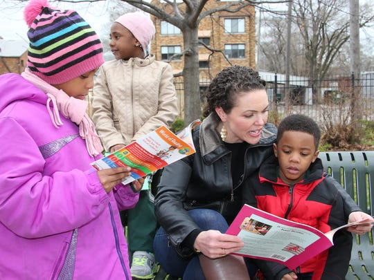 University of Detroit Mercy associate professor Mary-Catherine Harrison reads at a Little Free Library event at Gesu School.