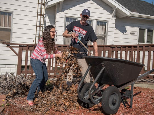 Aubrianna Caldwell, 8, helps her dad, Dion Caldwell, in their front yard doing spring clean-up on Sunday.