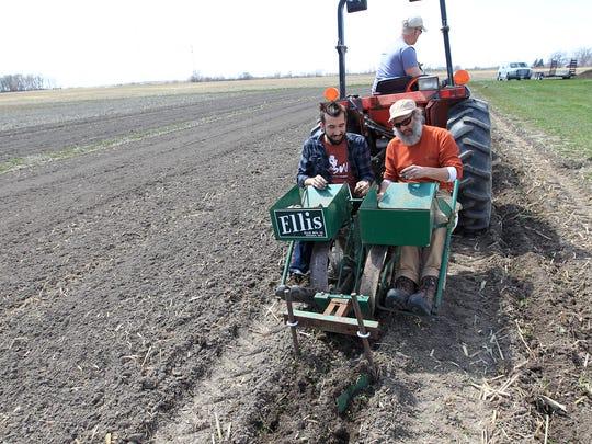 John Boller, left, and Scott Koepke plant potatoes