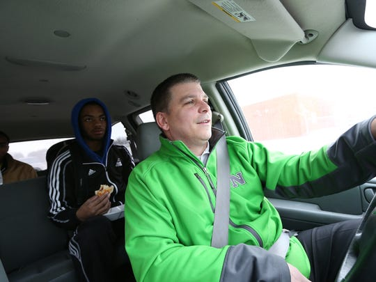 Des Moines North varsity basketball coach Chad Ryan drives students Neico Greene, center, and Samuel Williams Jr., to school on Tuesday, Jan. 7, 2014, in Des Moines, Iowa.
