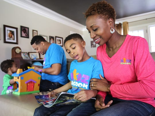 Danielle North, 33, reads a book with one of her sons, Eugene North Jr., 6, while Eugene North Sr. 34, plays with their other son Preston, 2, at their home in Detroit on Thursday, May 5, 2016. Danielle and her husband are opening an indoor playground called Kidz Kingdom that is inspired by their children.