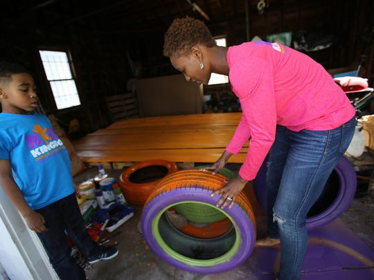 Danielle North, 33, of Detroit is painting the parts of a treehouse she is building in her garage for her new business, Kidz Kingdom, while her son, Eugene Jr., 6, watches on Thursday May 5, 2016.