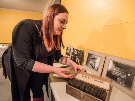 Heather Stratton, Education and Outreach Manager at Kingman Museum shows some hand-painted glass slides as part of a photography exhibit.