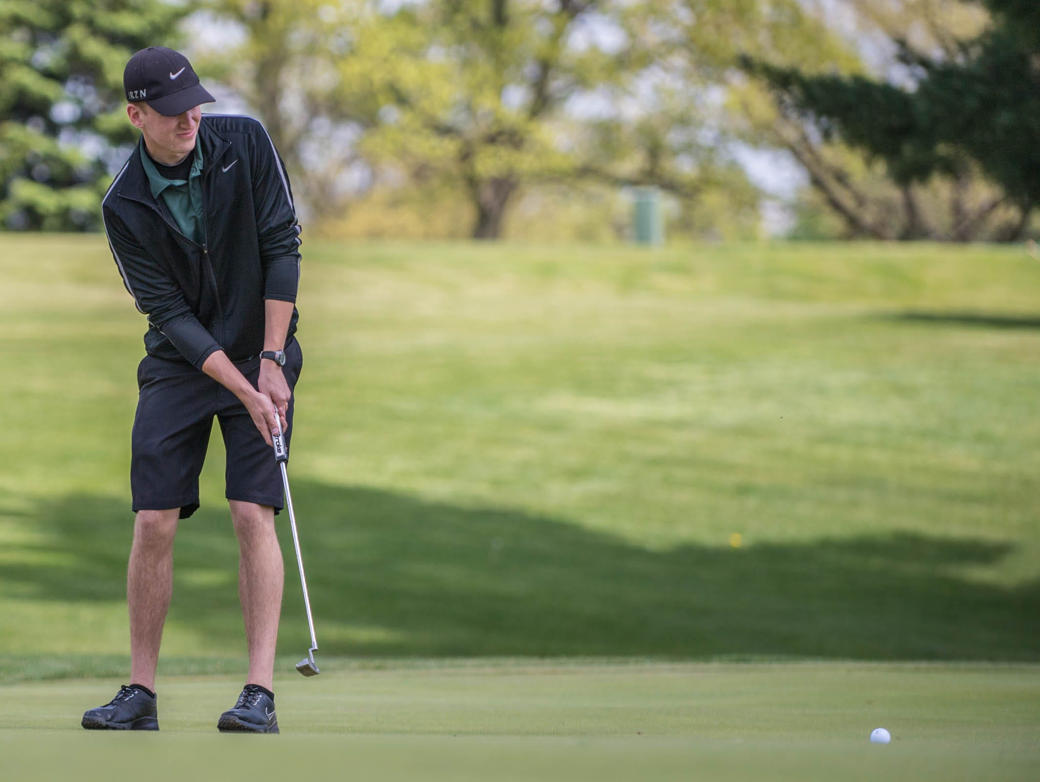 Pennfield senior Chase Williamson hits his putt during All-City Golf Tournament at Riverside Golf Club on Friday.