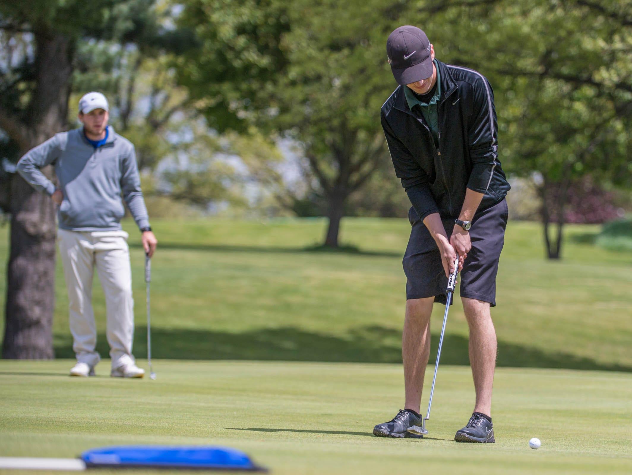 Pennfield senior Chase Williamson hits putts during All City High School Golf at Riverside Golf Club on Friday. Harper Creek junior Alex Johnson waits his turn.