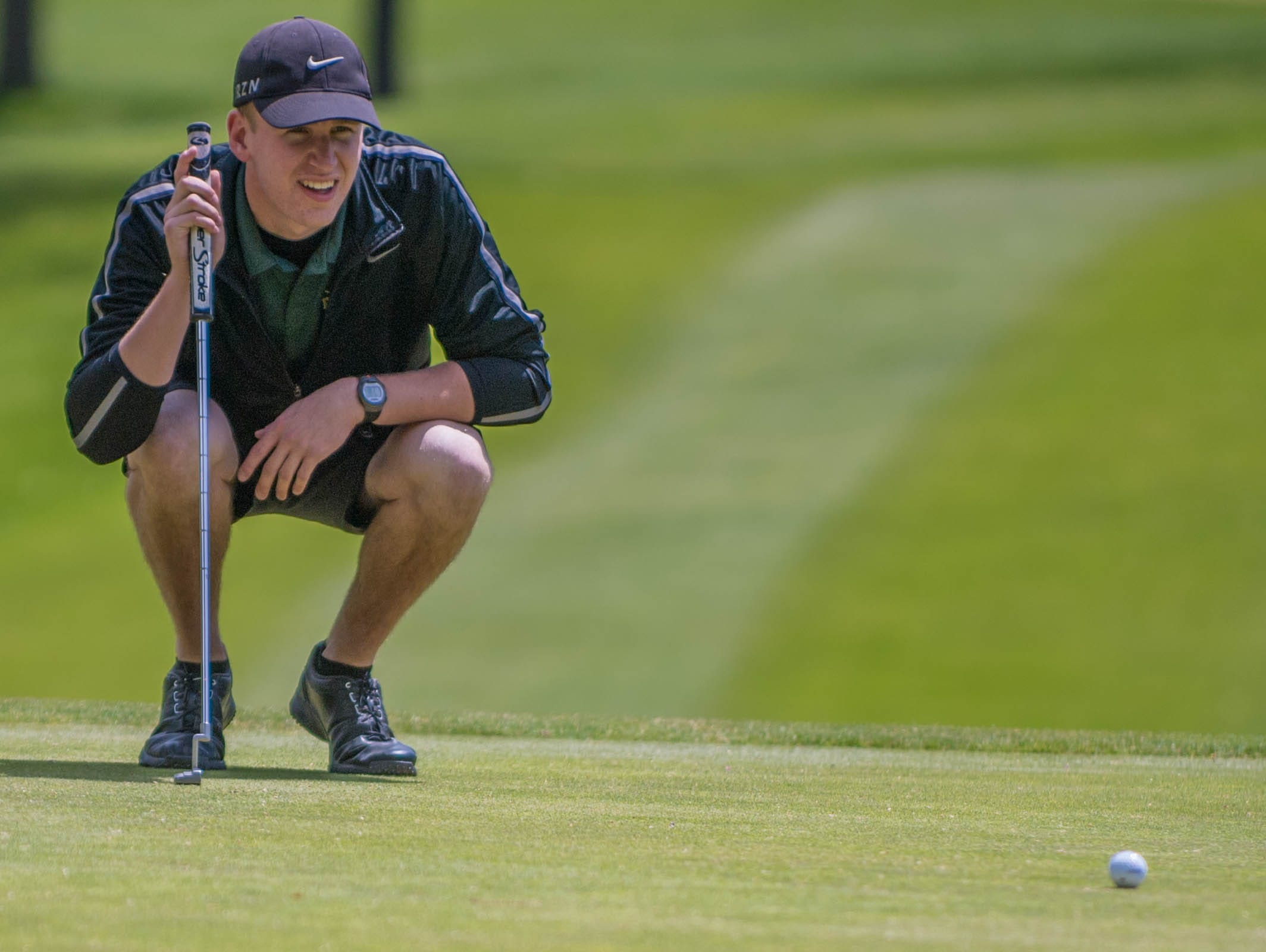Pennfield senior Chase Williamson reads the green during All City High School Golf at Riverside Golf Club on Friday.