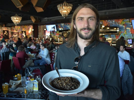 Theo Kozerski, 27, is the co-founder of Detroit Ento, a local edible-insect startup. He's pictured with a bowl of roasted crickets at the Knowledge on Tap event April 19, 2016, at HopCat in Midtown Detroit.