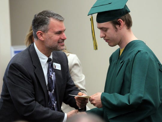 Iowa City Community School District Superintendent Stephen Murley hands Garth Ratchford his diploma during the Transitions Services Center graduation ceremony at the Iowa City Community School District offices on Wednesday, May 18, 2016.