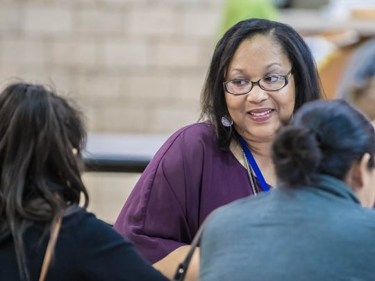 Niaka Dunbar, Battle Creek Public Schools' family and community engagement coordinator, talks to students and parents during a literacy fair at Verona Elementary earlier this month.