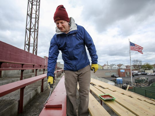 Detroit City Football Club co-owner Todd Kropp, 37, of Detroit paints the recently renovated bleacher maroon at Keyworth Stadium in Hamtramck on Sunday, May 15, 2016.