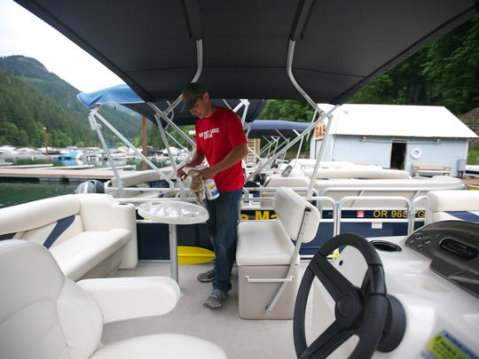 Braeden Cook, 19, cleans one of the rental boats at Detroit Lake Marina on Thursday, May  26, 2016.